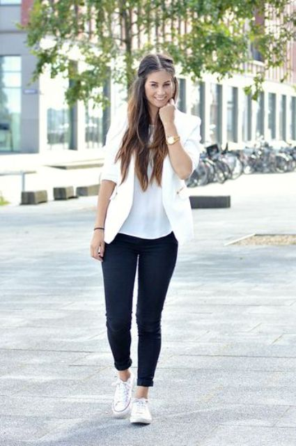 black jeans, a white top and blazer and white Converse