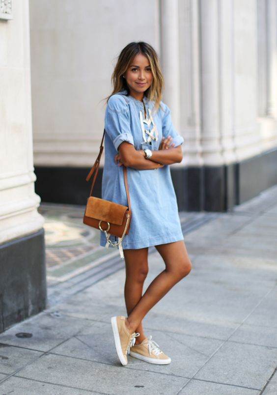a chambray dress with lacing, neutral sneakers and an ocher crossbody bag