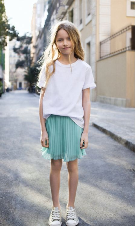 a mint pleated skirt, a white tee and grey Converse