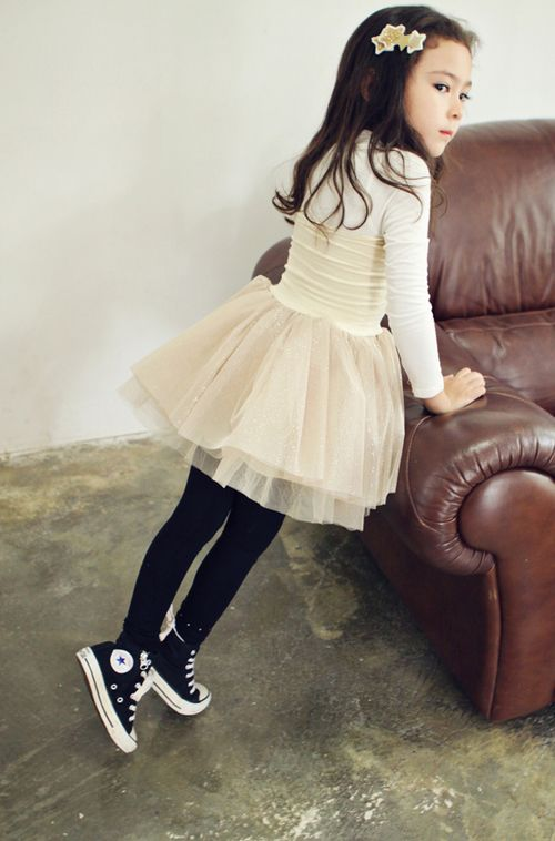 an ivory top wit long sleeves, an ivory tutu, black leggings and black Converse