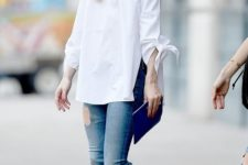 06 ripped jeans, a white off the shoulder top, white printed sneakers by Olivia Palermo