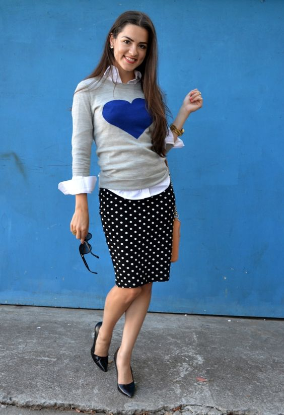 a polka dot skirt, a graphic sweater over a button up
