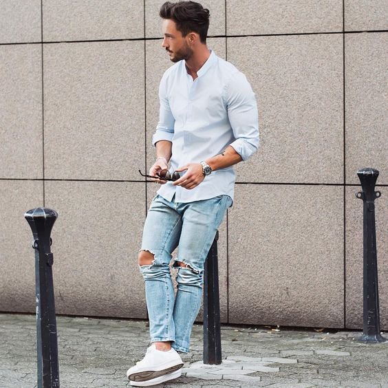 ripped blue jeans, a light blue shirt and white sneakers