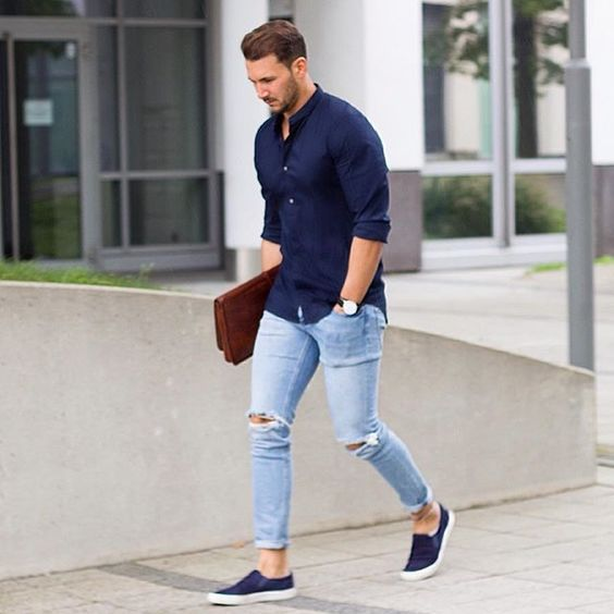 ripped blue jeans, a navy shirt and navy slip ons
