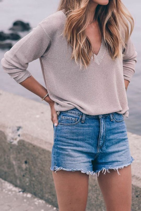 blue denim shorts and a neutral long sleeve with a V-cut