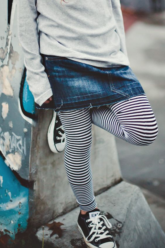 black converse, black and white striped leggings, a denim skirt and a grey sweatshirt