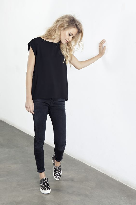 black jeans, a black sleeveless top and leopard slip ons