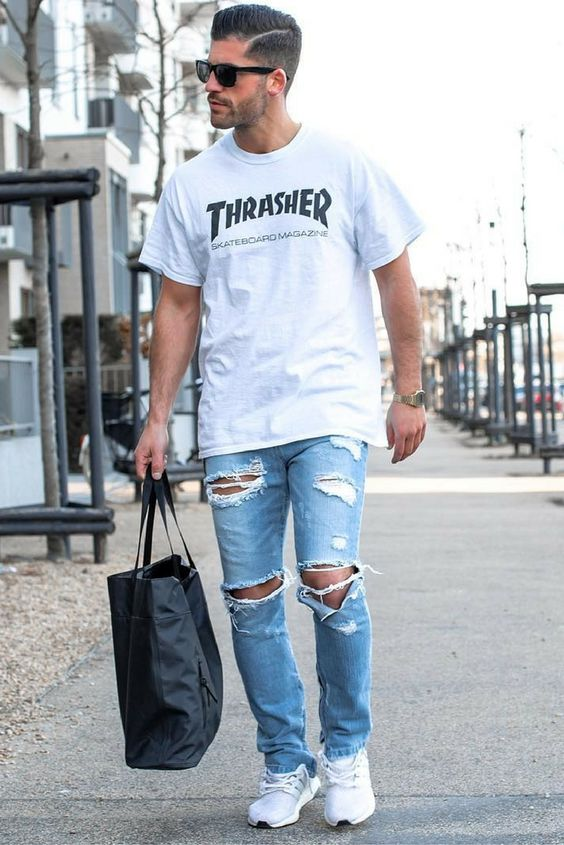 ripped blue jeans, a printed t-shirt and white trainers