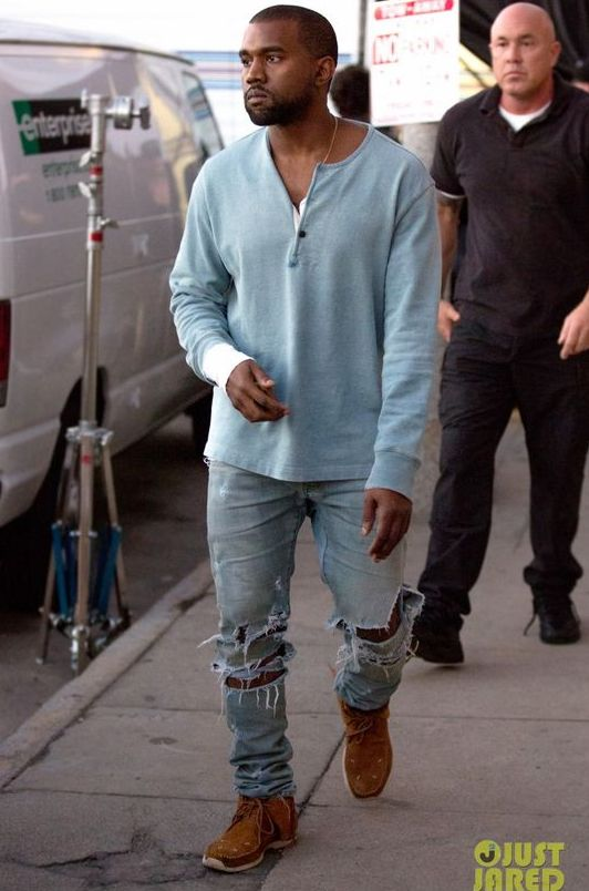 Kanye West rocking ripped blue denim, ocher moccasins and a light blue long-sleeve