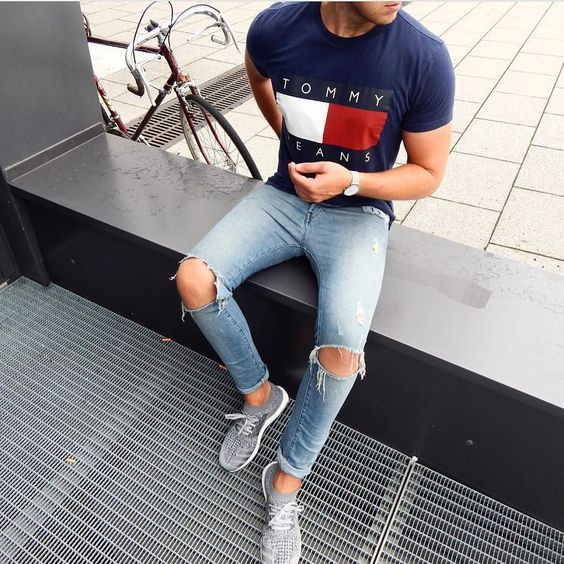 grey trainers, a printed navy t shirt, ripped blue denim