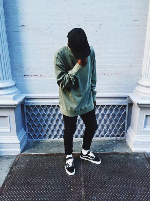 black jeans, a green sweatshirt, black Vans and a black cap