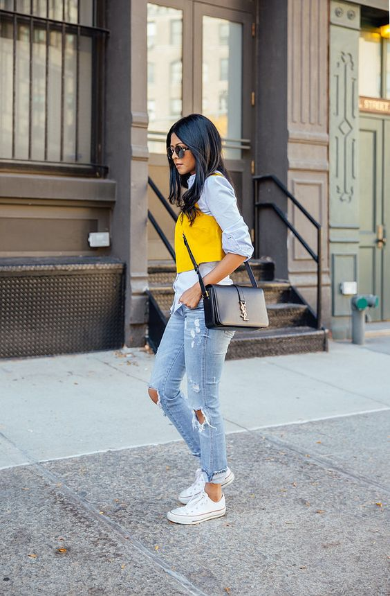 ripped denim, a shirt with a yellow vest and white Converse