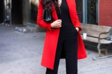 14 a black jumpsuit with a cutout and a red coat are enough for a holiday look