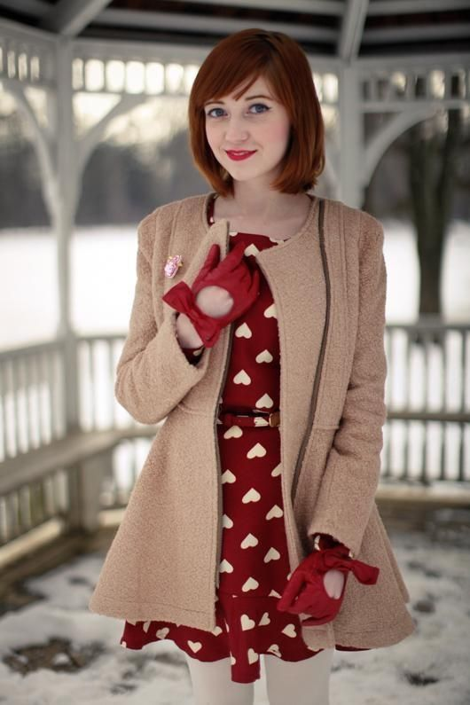 red heart-print dress, gloves and a tan coat