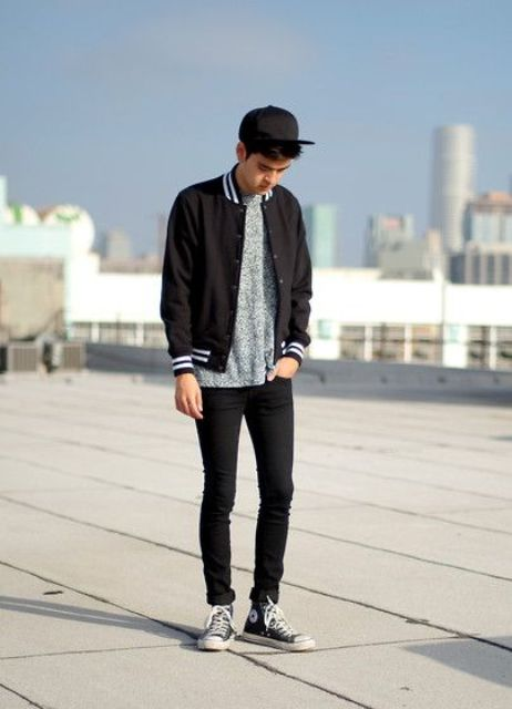 black jeans, a printed shirt, a black bomber jacket and black Converse