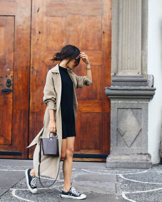 a black dress, a beige trenchcoat and navy Converse