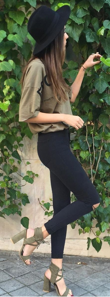 black ripped denim, an army green tee and suede heels, a black hat