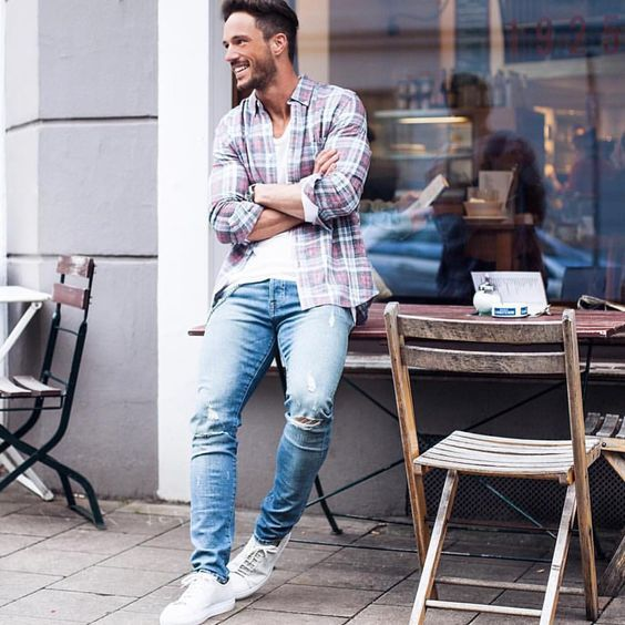 casual spring outfit with ripped blue jeans, a white tee, a plaid shirt over it