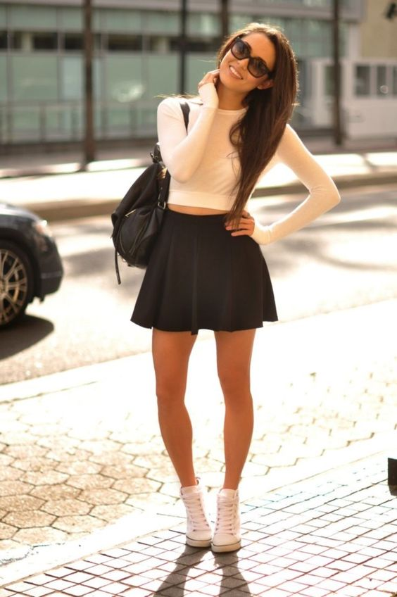 a black skater skirt, an ivory sweatshirt and white Converse