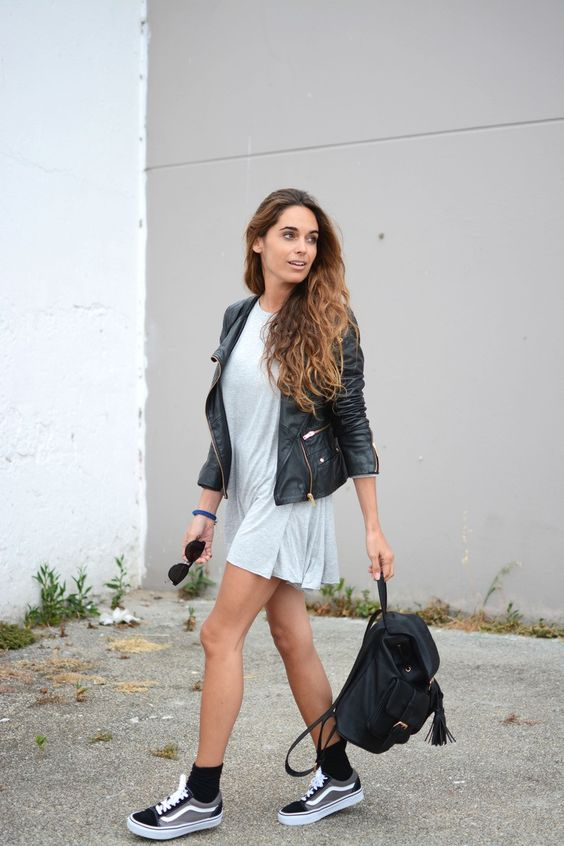 a light blue dress, a leather jacket, black and grey Vans