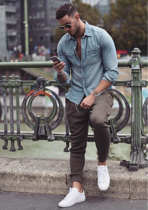 brown pants, a chambray shirt and white sneakers