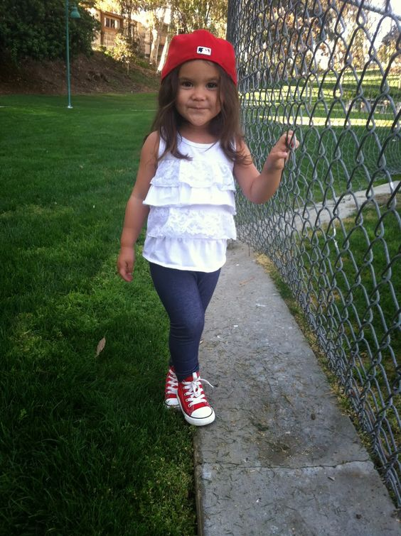 navy skinnies, a white ruffled top, red Converse