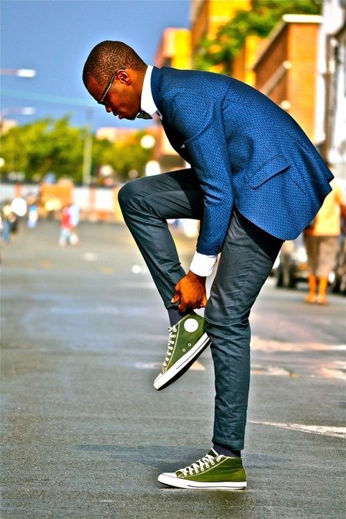 grey pants, a blue jacket and green Converse