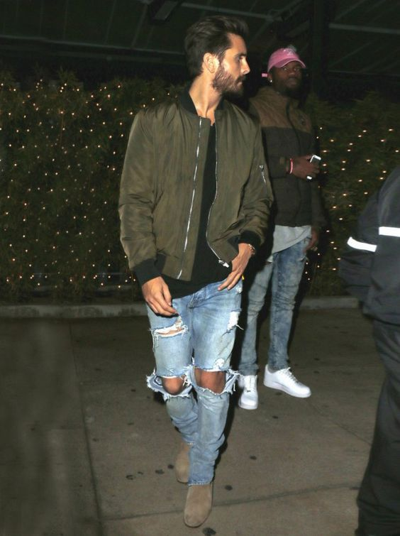 ripped blue jeans, suede boots, a black tee and an army green bomber jacket