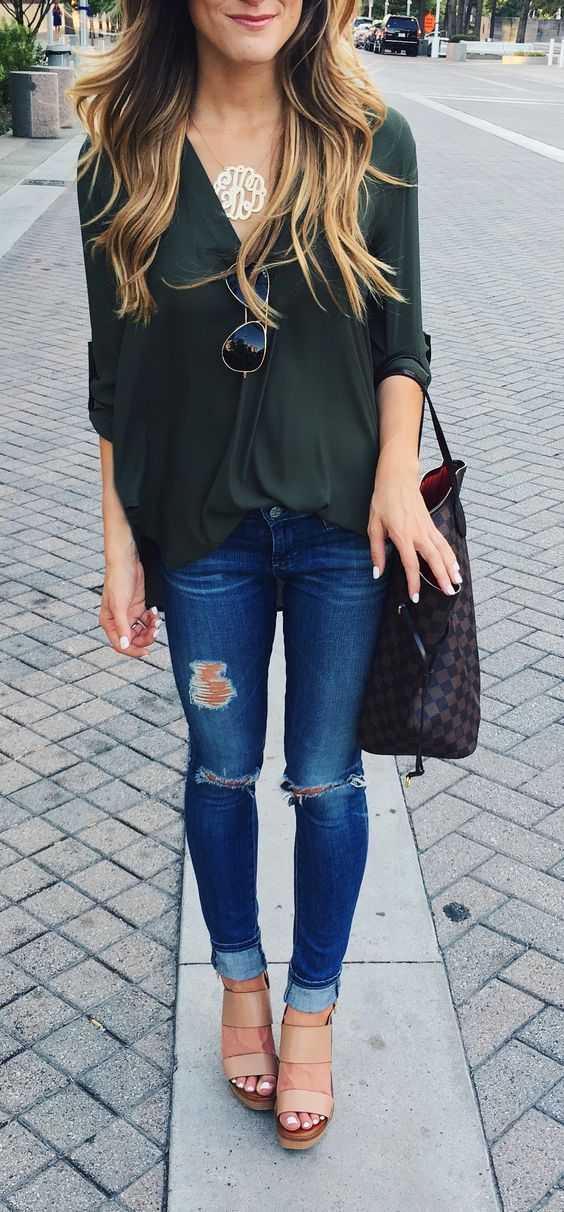 ripped jeans, an army green shirt and neutral shoes
