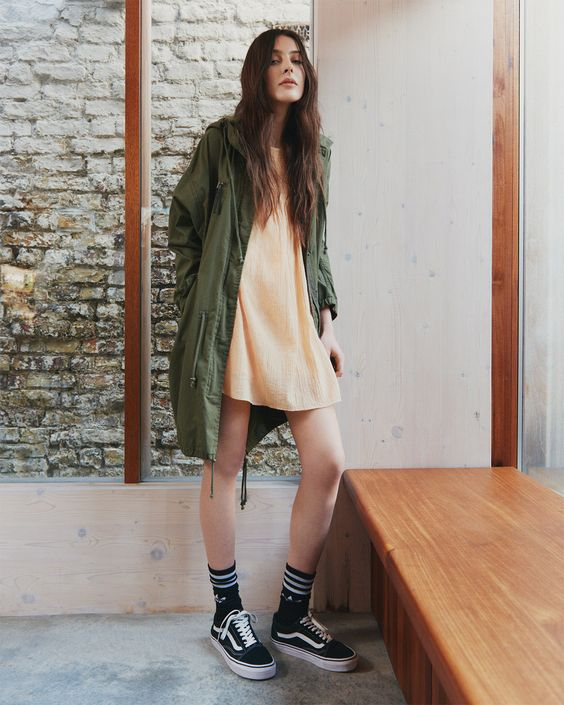 yellow mini dress, an army green parka, black Vans