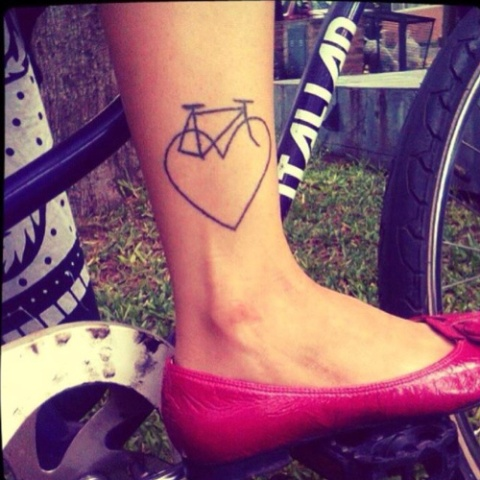 Bicycle and heart tattoo on the leg