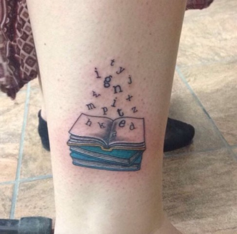 Book with flying letters tattoo
