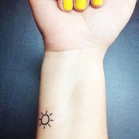 Tiny sun tattoo on the wrist