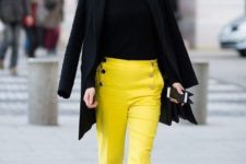 With black turtleneck, black coat, classic pumps and eye-catching necklace