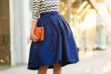 With chevron shirt, A-line midi skirt and orange clutch