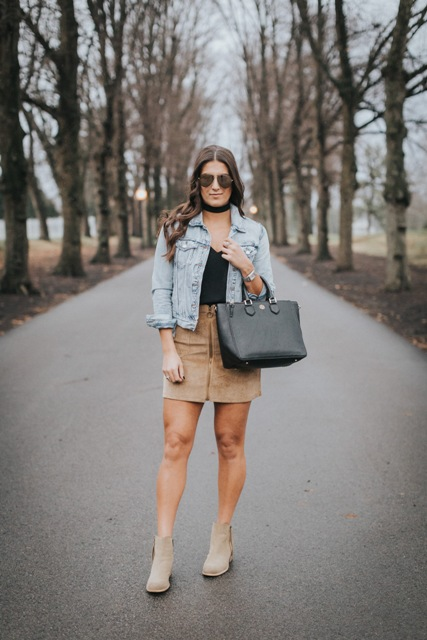 With denim jacket, black shirt and beige boots