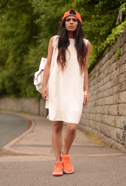 With loose dress, white backpack and orange cap