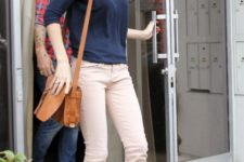 With navy blue shirt, golden flats and brown bag