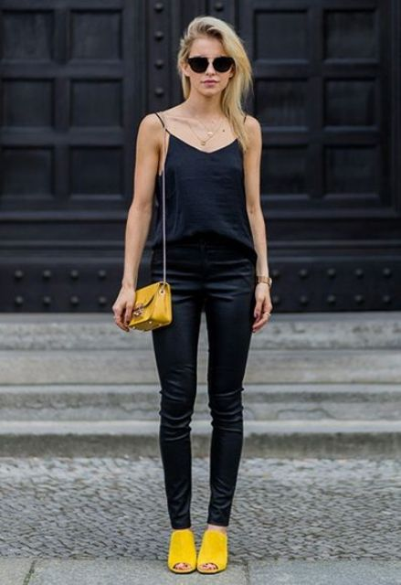 With navy blue top, black trousers and yellow mini bag