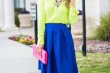 With neon yellow shirt, cobalt blue skirt and pink clutch