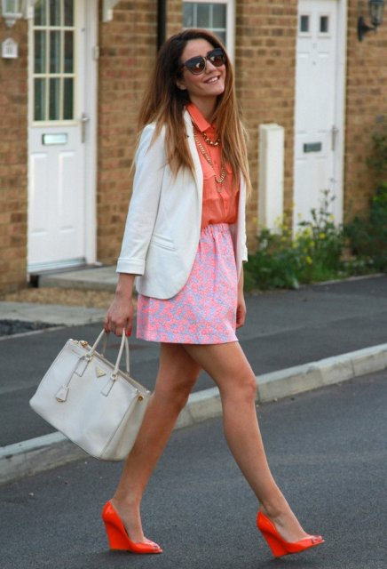 With orange shirt, pink printed skirt, white blazer and white bag