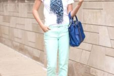 With printed scarf, white shirt, beige shoes and blue bag