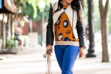 With printed sweatshirt, leather jacket, cream bag and black shoes