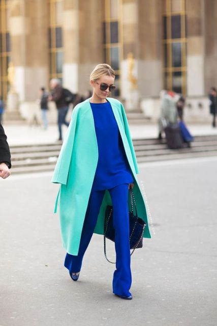 With turquoise coat, black bag and blue shoes