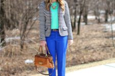With turquoise shirt, striped jacket and brown bag