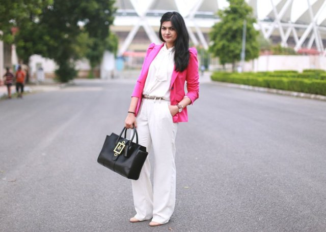 With white blouse, wide-leg pants and black bag