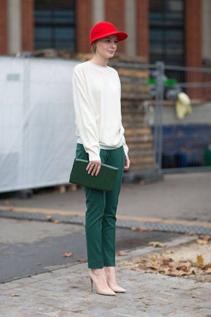 With white sweatshirt, red cap, green clutch and beige pumps