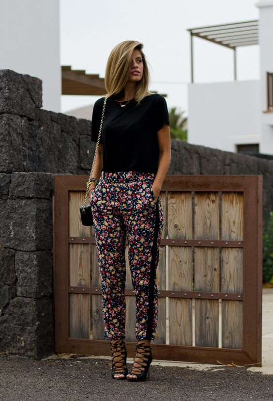 a black tee, dark floral pants and black lace up heels