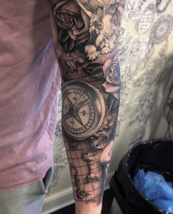 a map sleeve tattoo with roses, a wolf and a compass