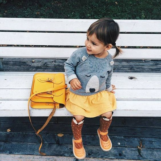 a yellow skirt and sandals, high socks and a grey sweatshirt with a bear